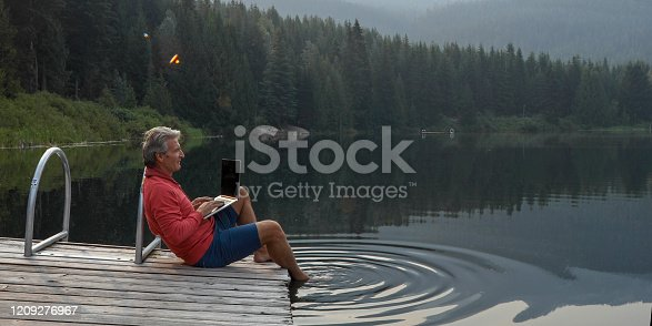 He uses laptop computer. Lost Lake, Whistler, BC