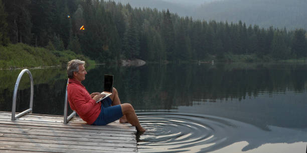 Mature man pauses on wooden pier, looks out across lake stock photo