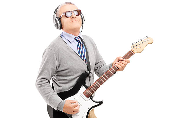 A mature man playing a guitar with headphones on stock photo