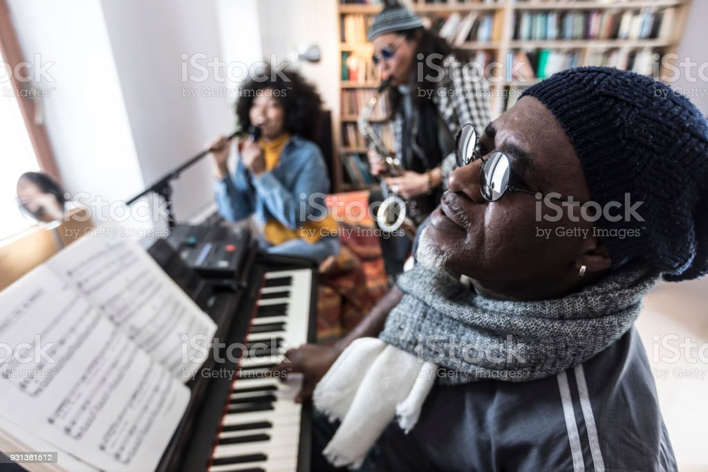 Mature man playing the piano with friends stock photo