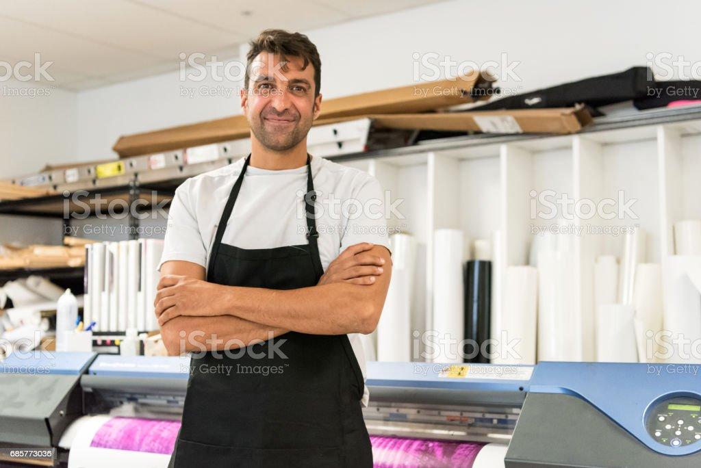 Mature man posing at his printing shop royalty-free stock photo