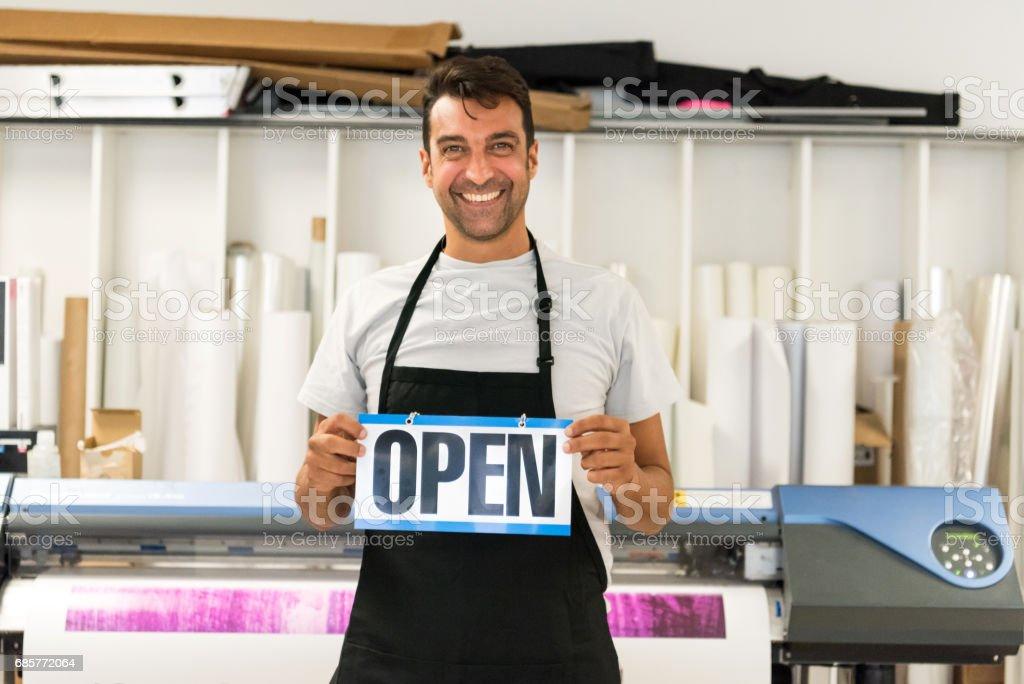 Mature man posing at his printing-graphic design shop royalty-free stock photo