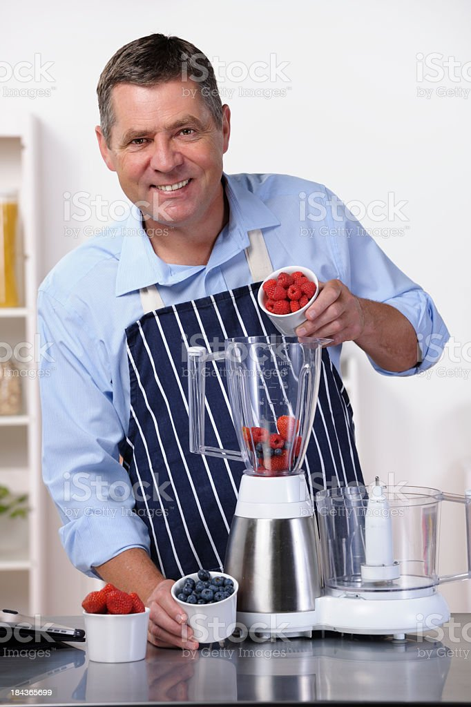 Mature Man Pouring Fruit Into Blender While Making Smoothie/ Dessert royalty-free stock photo