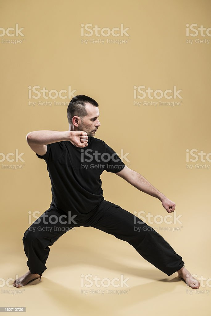 Mature man practices Tai Chi, studio shot, isolated royalty-free stock photo