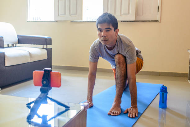 Mature man practices yoga at home watching video tutorial on smartphone stock photo