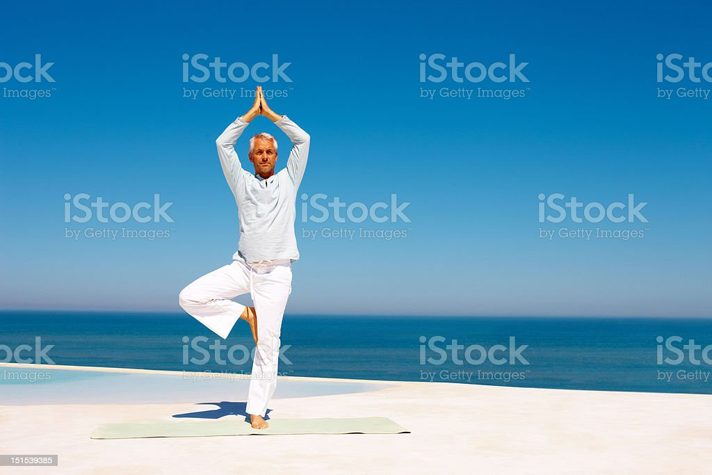 Mature man practicing yoga at beach stock photo