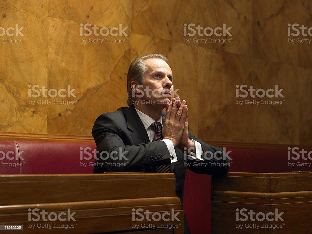 Mature man praying in pew royalty-free stock photo