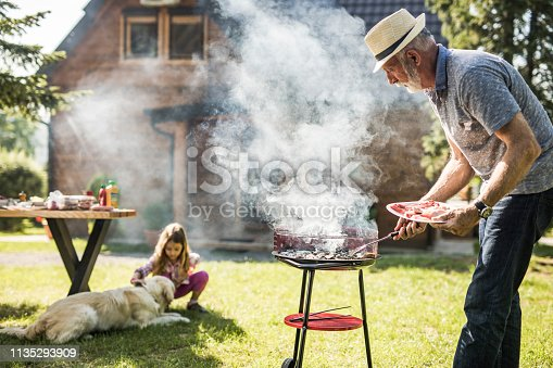 istock Mature man preparing barbecue for his grandkid in the backyard. Focus is on man. 1135293909