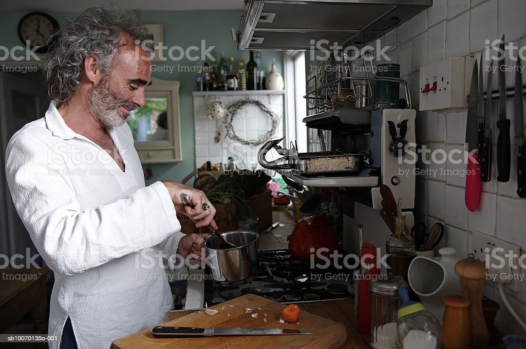 Mature man preparing food in kitchen 免版稅 stock photo