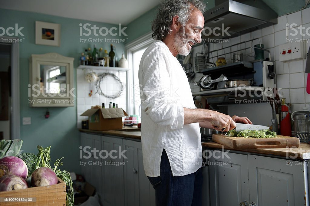 Maduro hombre preparando la comida en la cocina foto de stock libre de derechos