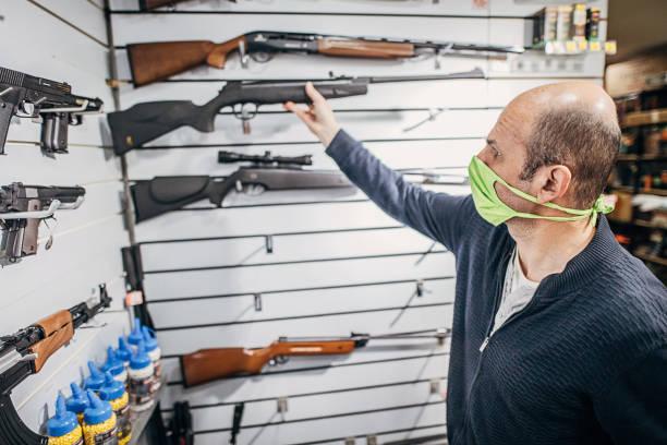 Mature man preparing his gun shop for opening stock photo
