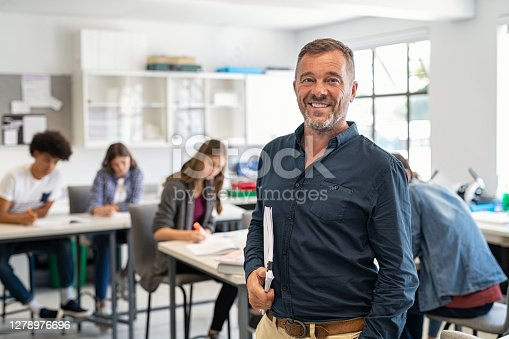 Portrait of mature teacher standing in university library and looking at camera with copy space. Happy mid adult lecturer at classroom standing after giving lecture. Satisfied high school teacher smiling and looking at camera while his studets studying in background.