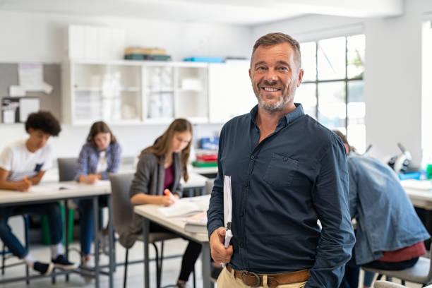 Mature man professor standing in class stock photo