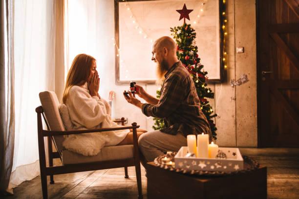 reifer mann schlägt mit engagment ring am weihnachtstag - verlobung was schenken stock-fotos und bilder
