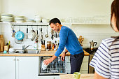 Mature man putting coffee mugs in dishwasher with his wife standing by