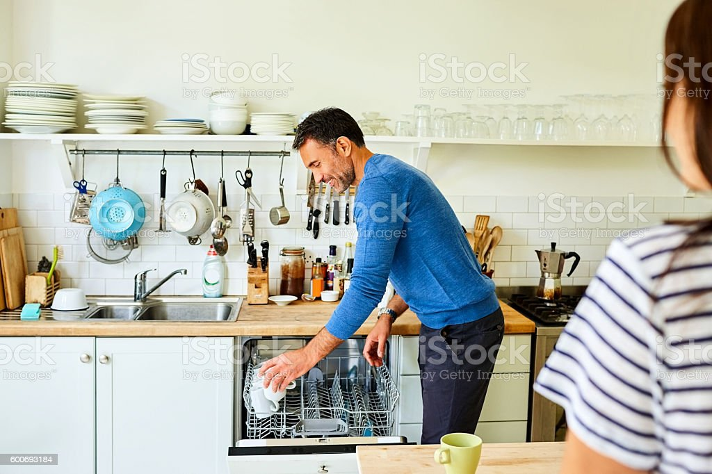 Mature man putting coffee mugs in dishwasher stock photo