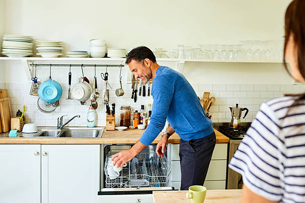 Mature man putting coffee mugs in dishwasher Mature man putting coffee mugs in dishwasher with his wife standing by stay at home father stock pictures, royalty-free photos & images
