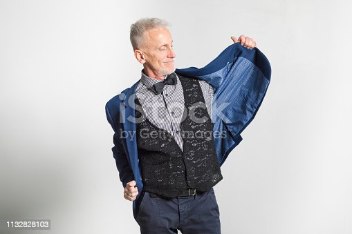 Mature man putting on his jacket smiling. Studio shot on a gray background.