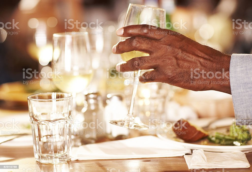 Mature man reaches for wine royaltyfri bildbanksbilder