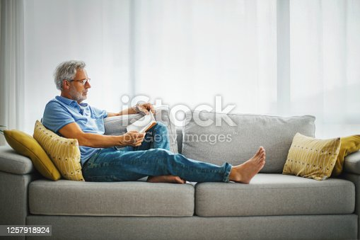 Mature man reading a book on the sofa.