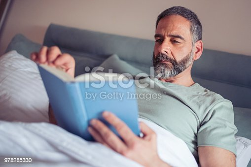 Mature man laying in bedroom and reading a book.