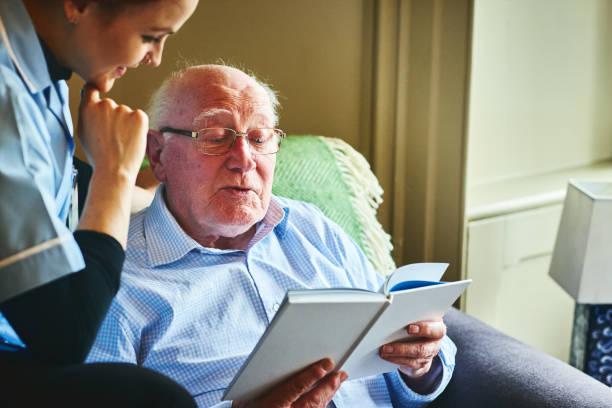 reifer mann ein buch mit nach hause betreuer - hospiz stock-fotos und bilder