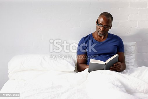 istock Mature man reading a novel on bed 528586843
