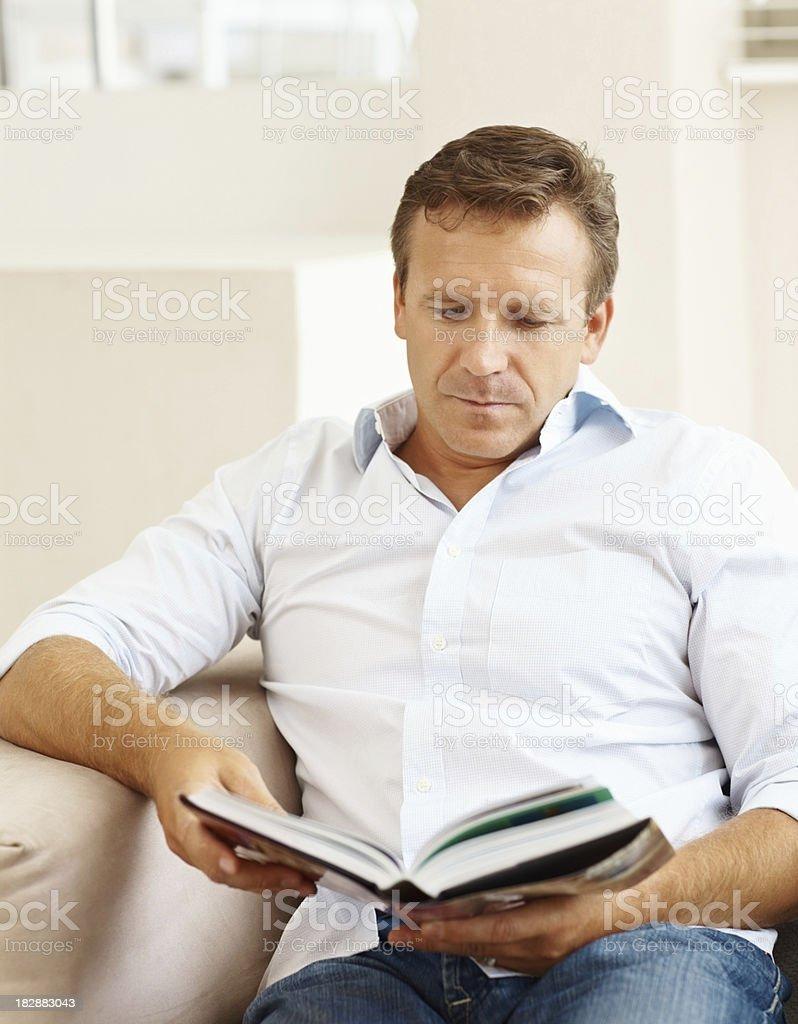 Mature man reading book at home royalty-free stock photo