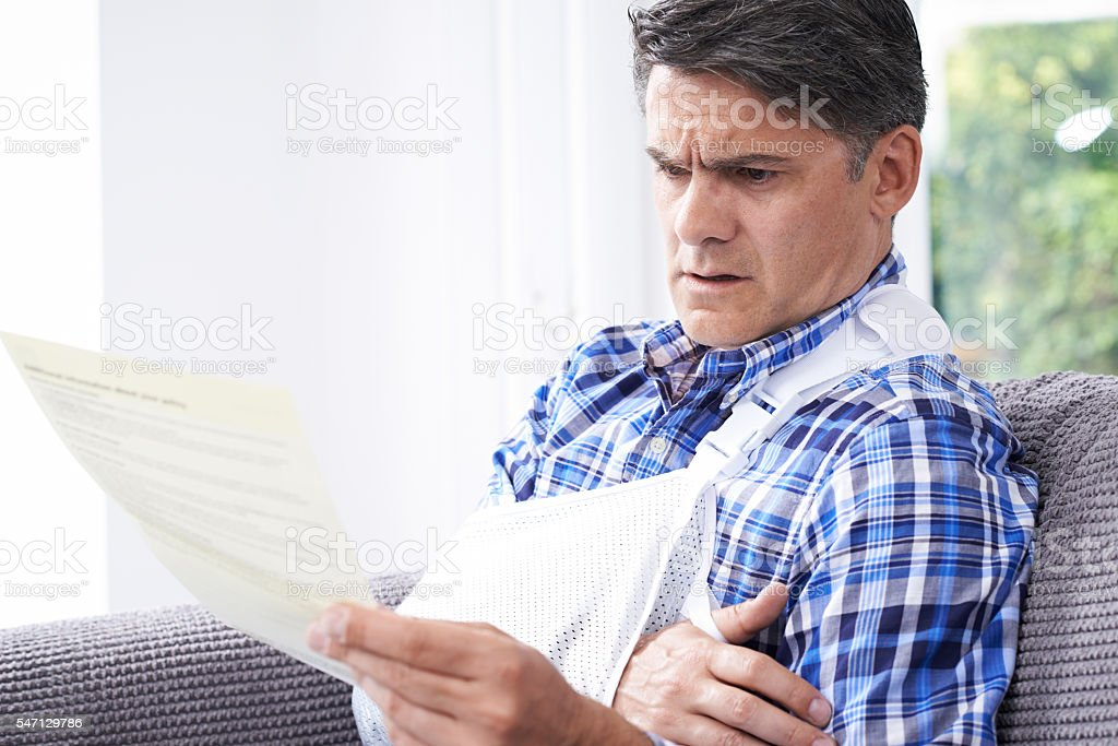 Mature Man Reading Letter About Injury stock photo