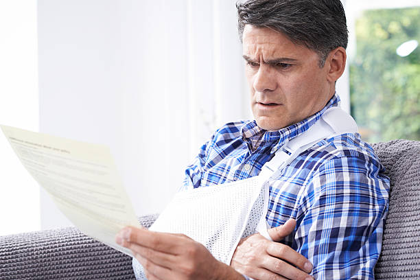 Mature Man Reading Letter About Injury - foto de stock