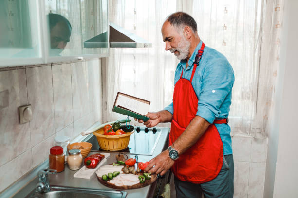 Mature man reading recipe and cooking in the kitchen stock photo