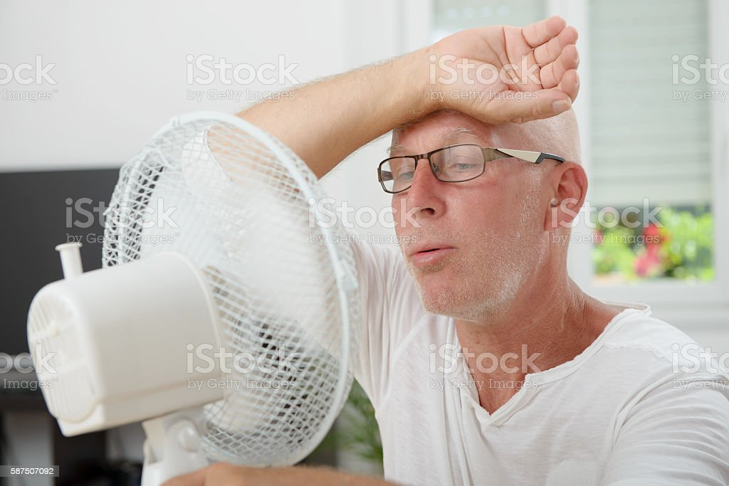 mature man refreshed with a fan stock photo