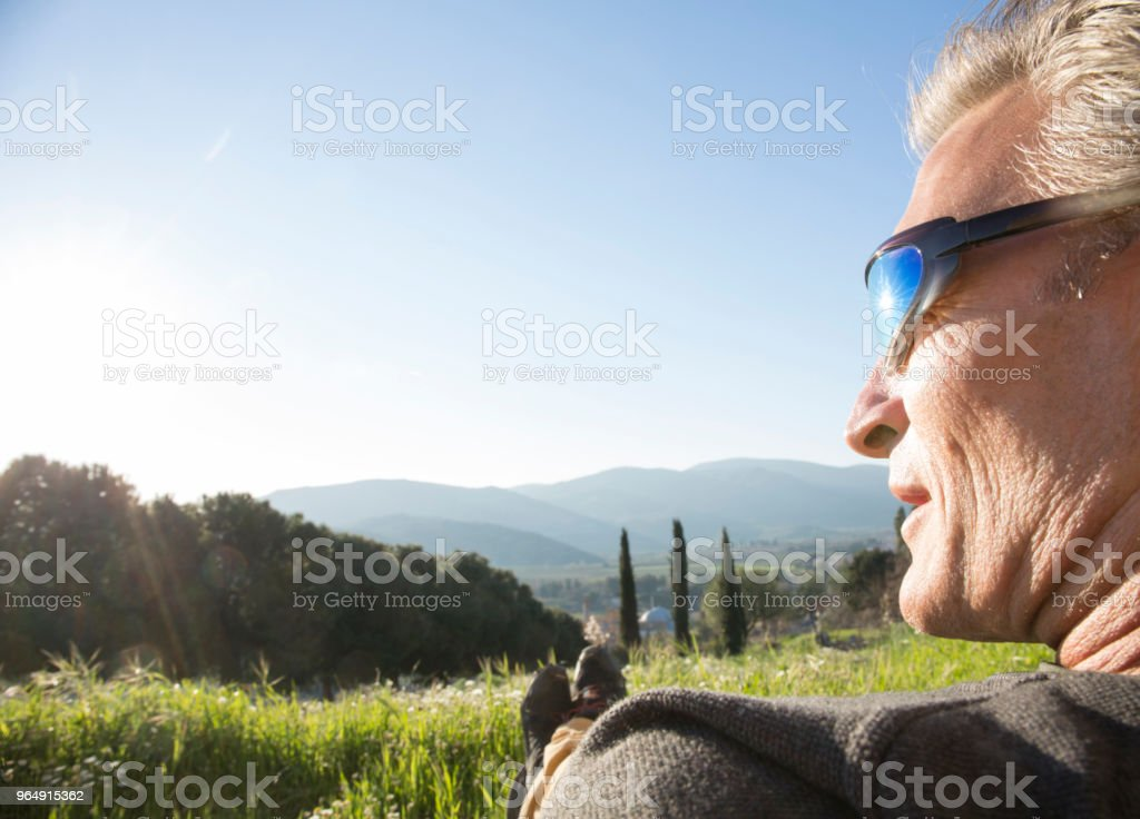 Mature man relaxes on hill crest in sunlight royalty-free stock photo