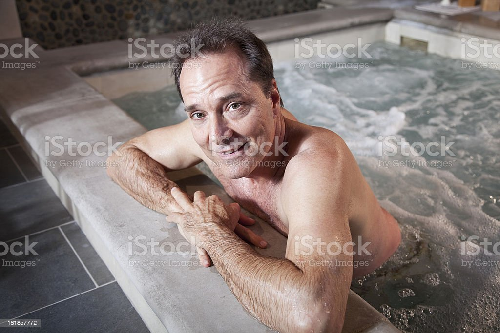 Mature man relaxing in hot tub stock photo