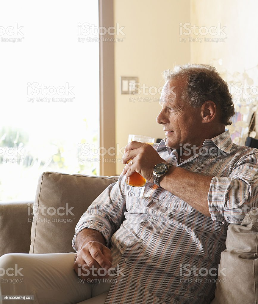 Mature man relaxing in living room having drink, smiling royalty-free stock photo