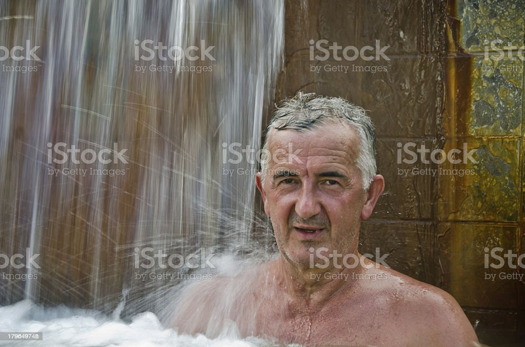 Mature man relaxing under hot spring royalty-free stock photo