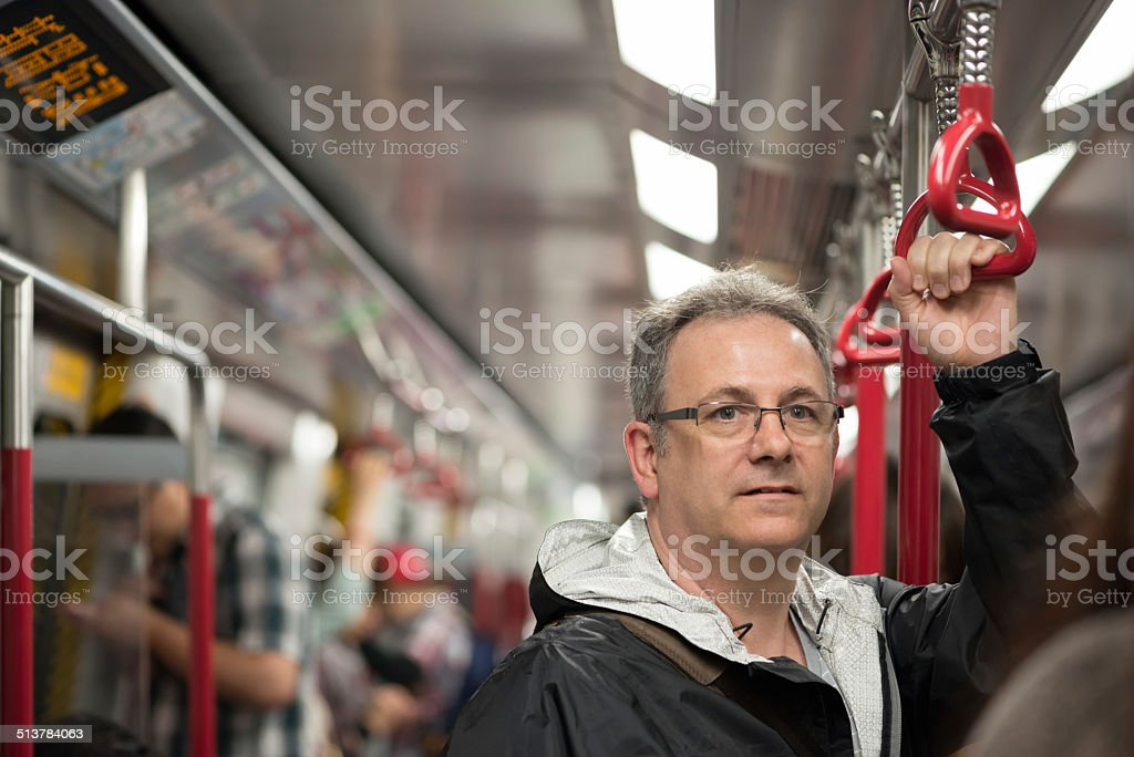 Mature Man Riding Train in Hong Kong stock photo