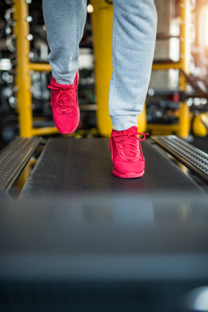 mature man running on a treadmill feet close up. - runner rehab gym foto e immagini stock