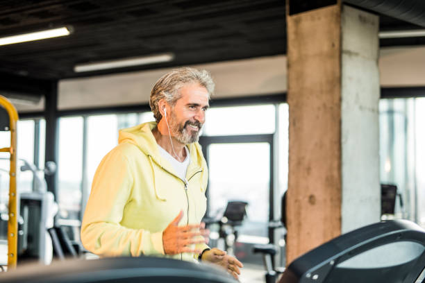 mature man running on a treadmill in a health club. - runner rehab gym foto e immagini stock