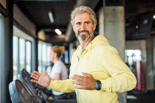 mature man running on a treadmill in the gym. - runner rehab gym foto e immagini stock