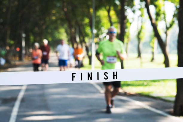 mature man running towards the finish line - finishing stock photos and pictures