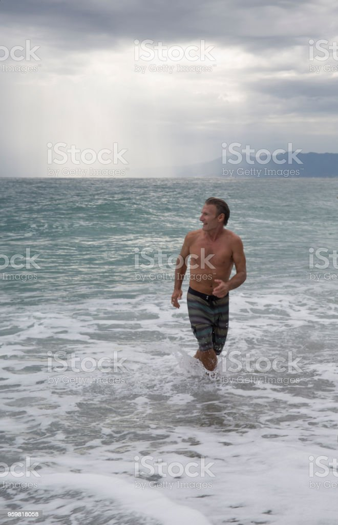 Mature man runs into waves stock photo