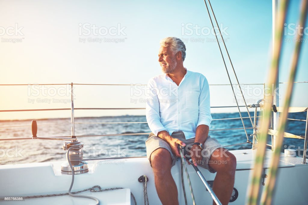 Smiling mature man sitting on the deck of his boat enjoying a sunny...