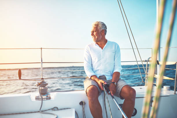 Mature man sailing his boat on the open ocean Smiling mature man sitting on the deck of his boat enjoying a sunny day sailing on the open ocean millionnaire stock pictures, royalty-free photos & images