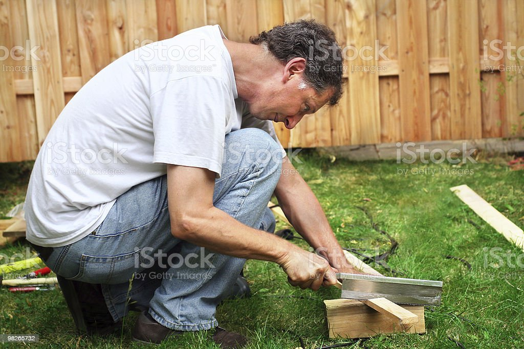 Mature man sawing piece of wood royalty-free stock photo