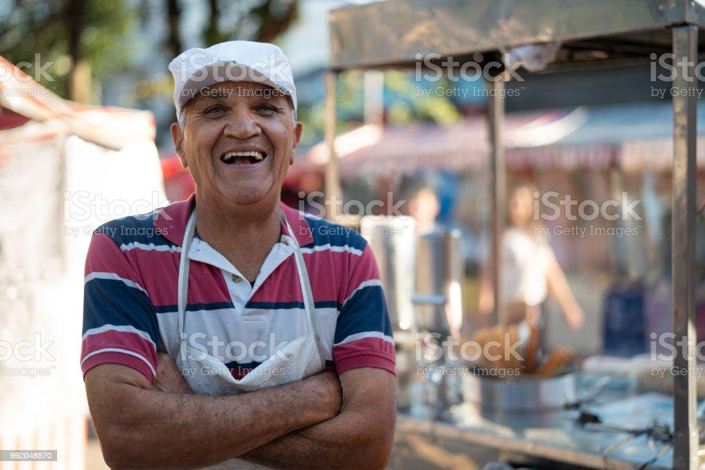 Mature Man selling churros at street portrait stock photo