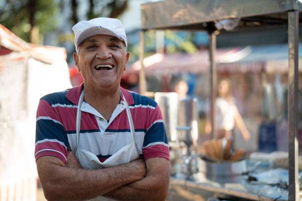 Mature Man selling churros at street portrait stock photo