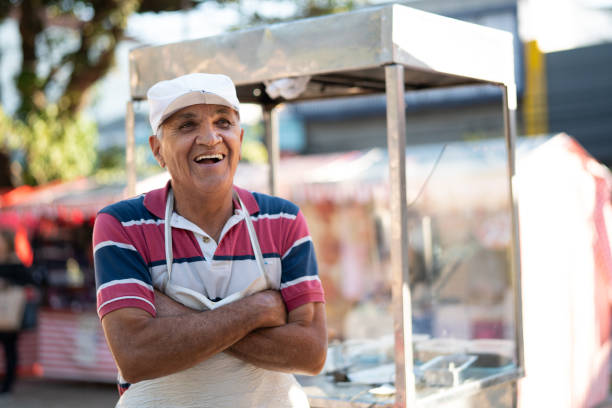 Mature Man selling churros at street portrait Small Business Owner market vendor stock pictures, royalty-free photos & images