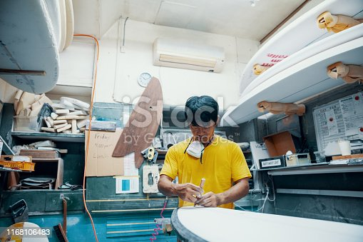 Mature man making and shaping a surfboard in his small business surf shop