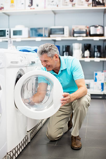 mature man shopping for a washing machine - happy person buy appliances stock photos and pictures